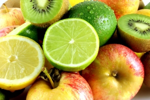 A colorful display of fresh fruits, limes, lemons, apples, kiwi